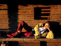 Sunset rest. Young tourist, resting at sunset, on a shepherd house in mountains Royalty Free Stock Image