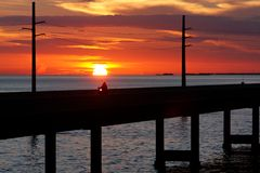 Sunset Ride. On 7 Mile bridge in the Florida Keys a motorcycle passes through the setting sun Stock Image