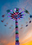Sunset Ride. People sitting suspended from an amusement park ride as it spins them above the crowds at the Wisconsin State Fair Royalty Free Stock Photography