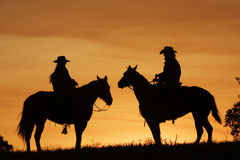 Sunset Riders. Silhouette of two western riders against amber colored sunset