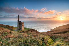 Sunset at Rinsey Head. Stunning sunset on the South West Coast Path as it passes the ruins of the Wheal Prosper engine house on cliffs at Rinsey Head, near stock image