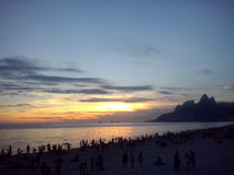 Sunset in Rio. A view of the sunset on Rio de Janeiro coast at Arpoador beach. At the back a mountain called Dois Irmãos, `Two Brothers Stock Images