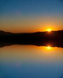 Sunset and rippling pond reflection. Stock Photos