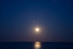Sunset and the rising of the moon on the Mediterranean coast in southern Spain. Royalty Free Stock Images