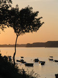 Sunset on the river. Beautiful sunset on the river bank, panorama glows with orange light, boats floating peacefully royalty free stock images
