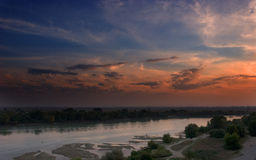 Sunset by the river. A beautiful sunset view by the banks of a slow-flowing river Stock Photography
