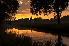 Sunset on a river. With village in the background Stock Photos
