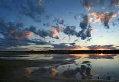 Sunset on the river. Beautiful sunset with multi-coloured clouds in the blue sky reflected in the river. The north of Russia stock photo