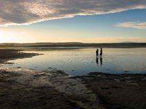 Sunset river. Children standing in the river watching the sunset Stock Photography