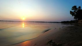 Sunset on the river bank. The Red Sun goes beyond the horizon on the beach stock video footage