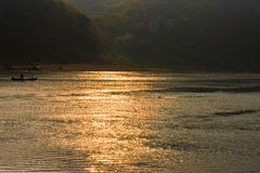 Sunset on River. A bright golden sunset on river with small boat in the sun ray reflections Stock Photo