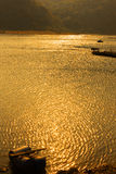 Sunset on River. A bright golden sunset on river with small boat in the sun ray reflections Stock Images
