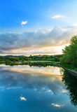 Sunset river. The colors of spring on the river Arno in Tuscany (Italy). The sky reflected on the quiet waters of the river creates a charming mirror effect Royalty Free Stock Photos