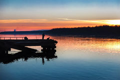 Sunset on the river, fishermen are fishing. The fishermen on the pier by the river. Beautiful view of the sunset. Shot backlit. The crimson sunset Royalty Free Stock Image