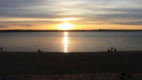 The sunset on the river. On the shoreline are silhouettes of lpeople stock footage
