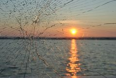 Sunset in river throw the broken glass royalty free stock images