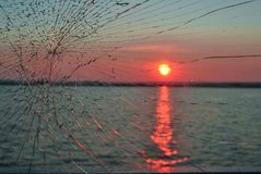 Sunset in river throw the broken glass royalty free stock photo