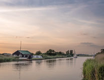 Sunset at The River Thurne Norfolk. The River Thurne Norfolk Broads. Dinghy tacking upwind in the background. Boat house and moored boats on the opposite bank Stock Photo