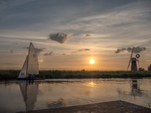Sunset at The River Thurne Norfolk. The River Thurne Norfolk Broads. Dinghy tacking upwind in the background. St Benet`s Drainage Mill on the opposite bank Stock Image