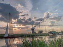 Sunset at The River Thurne Norfolk. The River Thurne Norfolk Broads. Dinghy tacking upwind in the background. St Benet`s Drainage Mill on the opposite bank Stock Photos