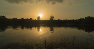 Sunset on the river., time-lapse. On the bank of trees, the wind stirs the water, the sky floating clouds. sunset on the lake, time-lapse stock video