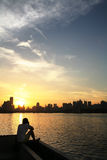 Sunset of riverside. Male figure sitting on the zhujiang  riverbank in front of the yellow sunset in guangzhou china. hi is taking photo Royalty Free Stock Photos