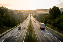 Sunset road. Highway traffic in sunset. Road goes through the hills Stock Photo