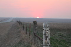 Sunset, Road and fences. Another beautiful sunset on the prairie Royalty Free Stock Image