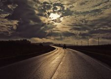 Sunset road glistens in the sun strives forward. royalty free stock images
