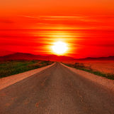 Sunset road. Red sunset and road aspiring in a distance Stock Photo