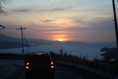 Sunset on the road to Cumana, Venezuela. Sunset on the road car just infront with electricty cabels to Cumana, Venezuela Royalty Free Stock Image