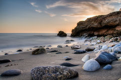 Sunset rocks on beach Stock Photography