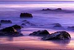 Sunset Rocks at California Beach. Rocks sit in the colorful sunset waters off the California Coast Royalty Free Stock Images
