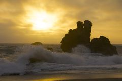 Sunset on the Rocks of the California Coast. A wave crashes on the rocks off shore at Sonoma Coast State Park in California as the sun sets through the foggy Stock Photos