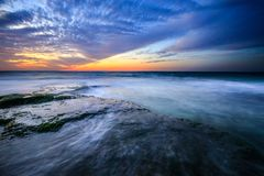 Sunset with rocks on the seashore. Sunset with the rocks on the beach in Gaza City stock photos