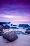 Sunset on the Rocks. Sunset on the west coast of Thailand taken using a long exposure to get silky waves Stock Photo