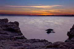 Sunset on the rocky beach Stock Photos