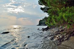 Sunset on a rocky beach. A cloudy, soft-lighted sunset on a beautiful beach called 'Heaven' (Paradeisos) near Neos Marmaras village, in Halkidiki (Greece stock photography