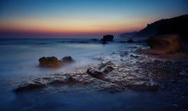 Sunset at rocky coast Stock Photos