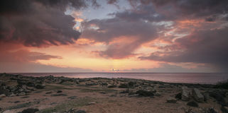 Sunset at rocky coast with a stormy red sky Royalty Free Stock Images