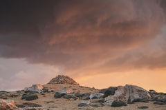 Sunset at rocky desert with a red cloudy sky Stock Photos