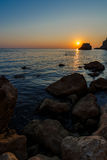 Sunset on the rocky seashore Stock Photography