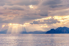 Sunset on a rocky seashore. Sunset on the coast, the sun's rays pass through clouds Royalty Free Stock Photo