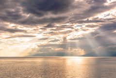 Sunset on a rocky seashore. Sunset on the coast, the sun's rays pass through clouds Stock Image