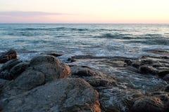 Sunset on the rocky seashore. Rocky seashore evening. Sunset wave Stock Image