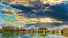 Sunset on a Romanesque bridge. An old Italian Romanesque bridge illuminated by the sun in a sunset at the end of spring Royalty Free Stock Images