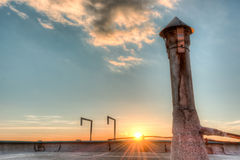 Sunset from a roof top with a roof vent Royalty Free Stock Photography