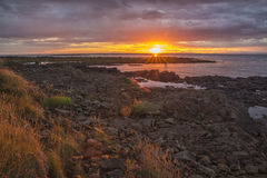 Sunset and rough rocky coast Stock Photos