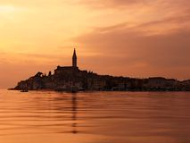 Sunset at Rovinj, Croatia. Late afternoon in Old Town Rovinj, Croatia (Europe). Seen from the yacht port. The highest object is the cathedral of St. Euphemia Stock Photo