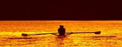 Sunset Rowers. Competitive rowing pair on lake Karipiro in the Waikato area of New Zealand Stock Photo